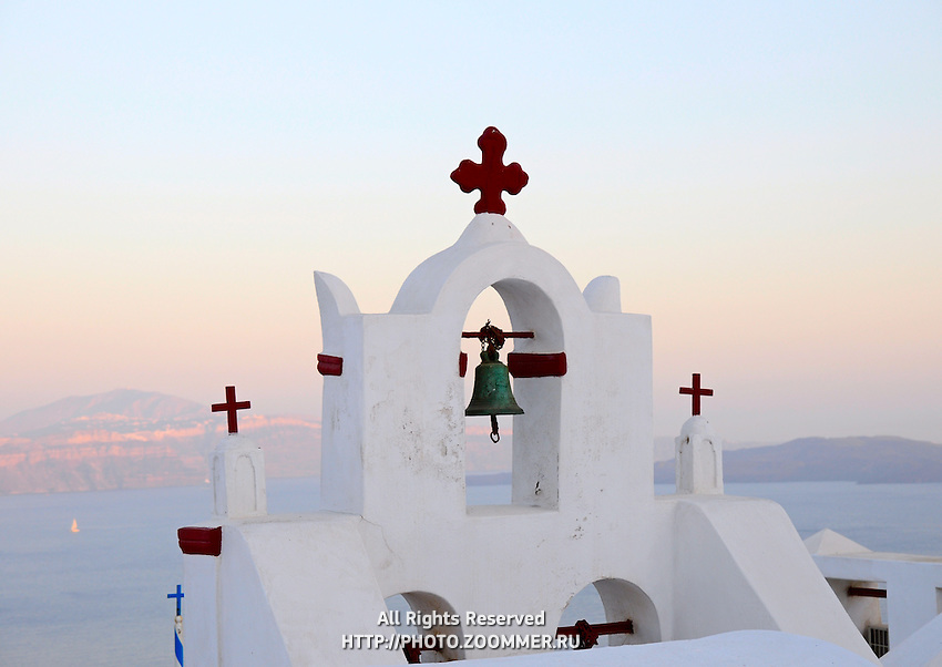 Whitewashed bell tower of orthodox church in Oia village Santorini