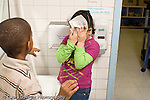 Education preschool 4 year olds girl covering her face with paper towel to escape boy who is teasing her horizontal