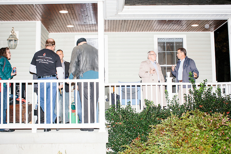 """People talk and smoke cigars after hearing Texas senator and Republican presidential candidate Ted Cruz speak at an event called """"Smoke a cigar with Ted Cruz"""" at a house party at the home of Linda & Steven Goddu Salem, New Hampshire. Cruz briefly smoked a cigar after speaking at the event."""