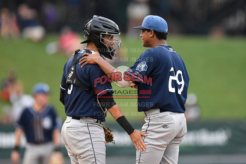 Starting pitcher Erick Julio (29) of the Asheville Tourists, right, talks with catcher Joel Diaz (5) during a game against the Greenville Drive on Wednesday, August 2, 2017, at Fluor Field at the West End in Greenville, South Carolina. Greenville won, 1-0. (Tom Priddy/Four Seam Images)