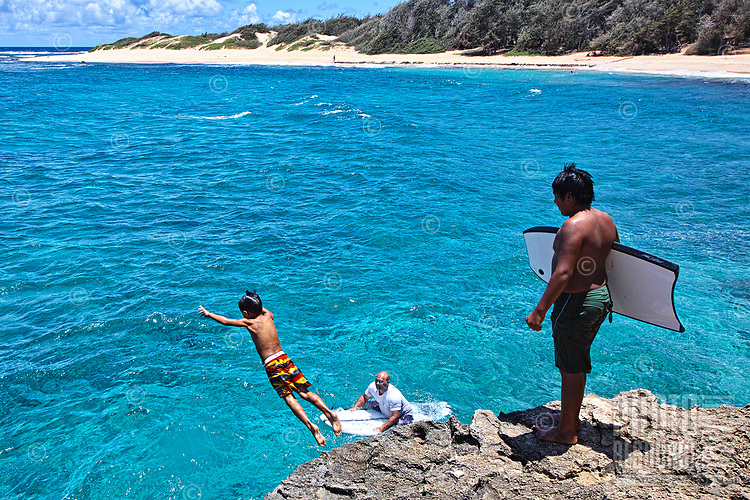 Two young boys take turns jumping off the rock at Kawailoa Bay near Po'ipu on the southeast shore of Kaua'i.