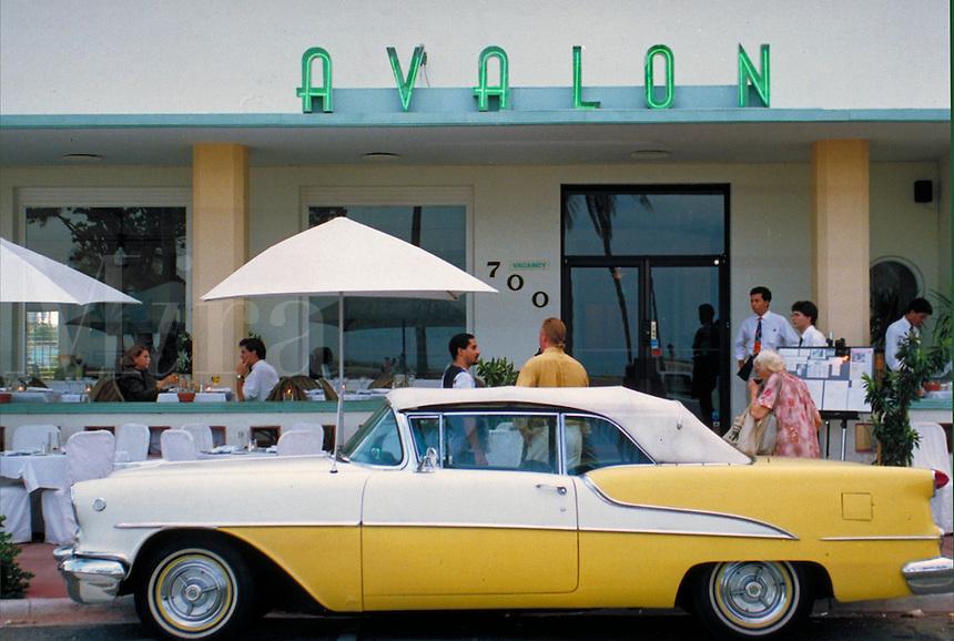 50s Scene with yellow car at Avalon, outdoor restaurant. Arch - Albert Anis, 1941. 700 Ocean Dr., M. Beach FL USA.