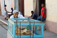 Man pushing a food cart along a street, Trinidad, Cuba.