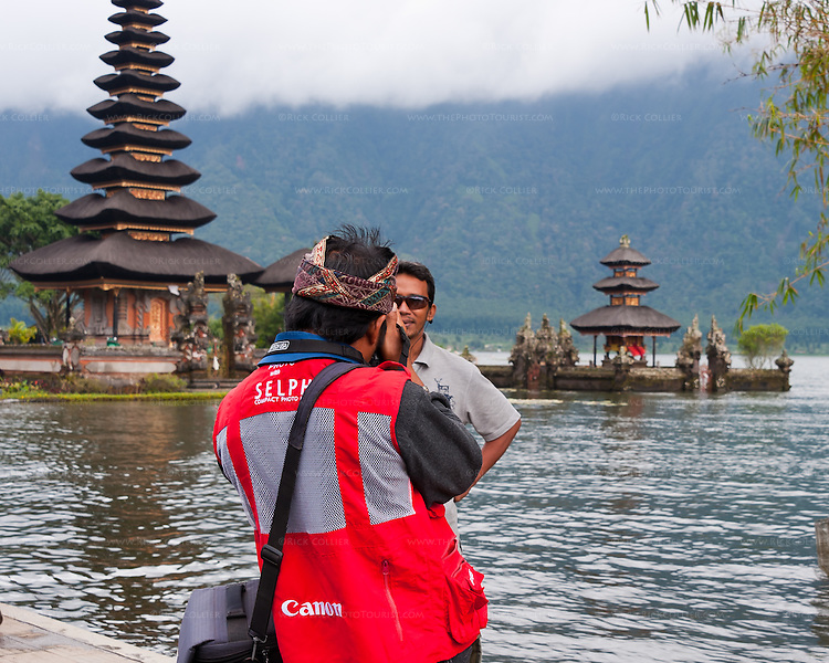 """One of the many local vendors takes a souvenir snapshot of a tourist by the lake, at the iconic spot in the grounds of the Hindu temple of Ulun Danu at Candikuning, on Bali, Indonesia.  Located in the high hills of the Bedugul, about 30 miles north of Bali's capital city of Denpasar, the temple is built on the shores of the crater Lake Bratan (formed from the sunken crater of a long-dormant volcano).  Much of the inner precincts of the temple is closed to the (non-Hindu) public, but the gardens are spectacular and feature fabulous shrines, statuary, and views.  The iconic tourist image is the two """"water shrines,"""" which these days are usually partially submerged in the waters of Lake Bratan."""