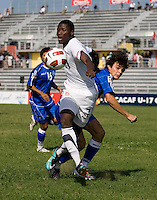 Alfred Koroma (7) of the United States is fouled by Olivier Ayala (15) of El Salvador during the quarterfinals of the CONCACAF Men's Under 17 Championship at Catherine Hall Stadium in Montego Bay, Jamaica. The USA defeated El Salvador, 3-2, in overtime.