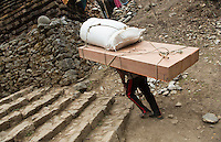 Nepal Himalayas  Porter carrying massive load through the streets of Phak Ding Solukhumbu remote Mt Everest   55 56