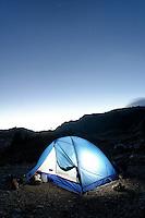 Backpacking tent glowing below night sky, near Yellow Aster Butte, North Cascades, Whatcom County, Washington, USA