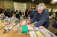 Jude Johnson writes the weight of a bag on postage mailers as a crew of volunteers, including a group from the Alaska Military Youth Academy, move, weigh and stack thousands of musher food drop bags that are headed to the 22 checkpoints along the trail at the Airland Transport facility in Anchorage, Alaska on Wednesday, February 17, 2016 just prior to Iditarod 2016