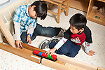 Education preschool 4 year olds two boys playing together with vehicles, car and Lego truck, and ramp and track they built from wooden blocks