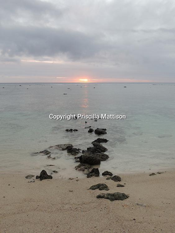 Rarotonga, Cook Islands - September 20, 2012:  Black rocks stretch from the beach into the lagoon.