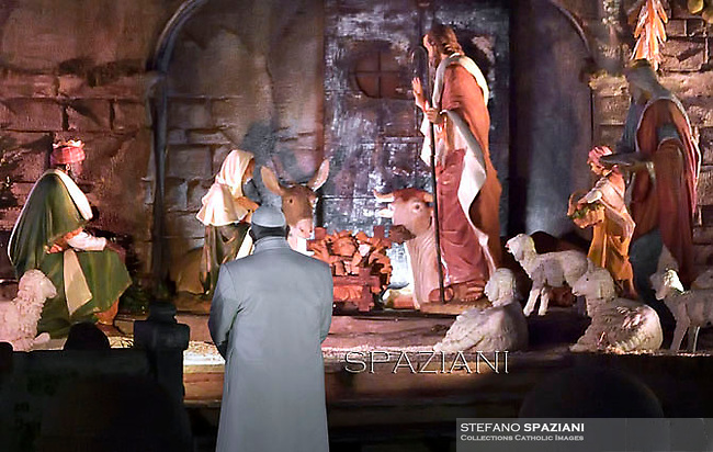 Pope Francis prays in front of a Nativity scene in St Peter's square at the Vatican on December 31, 2014