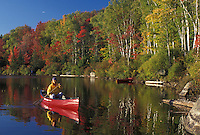 canoeing, canoe, Vermont, VT, Woman paddles a red canoe on the calm waters of Kettle Pond in Groton State Forest in the fall.