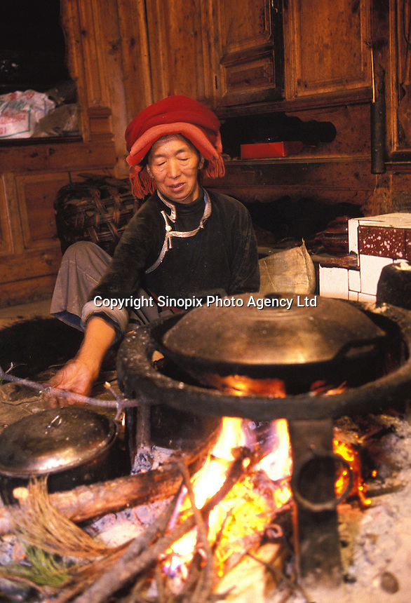 "A matriarch cooks in her traditional home on Lugu Lake in Yunnan. Matriarchs take their traditional place which is always on the left of the fire place. Women from the Mosuo tribe do not marry, take as many lovers as they wish and have no word for ""father"" or ""husband"". But the arrival of tourism and the sex industry is changing their culture...PHOTO BY SINOPIX"