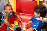Education Preschool 3-4 year olds boys wearing smocks at water table playing talking and interacting