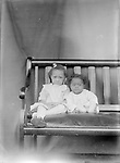SISTERS AND BROTHERS. The pair of children seated on the fine settee with a leather cushion are probably sister and little brother.<br /> <br /> Photographs taken on black and white glass negatives by African American photographer(s) John Johnson and Earl McWilliams from 1910 to 1925 in Lincoln, Nebraska. Douglas Keister has 280 5x7 glass negatives taken by these photographers. Larger scans available on request.