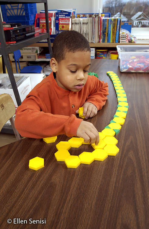 MR / Schenectady, NY.Yates Arts-in-Education Magnet School.Grade 1 - Grade 2 split classroom.Boy (6, grade 1, African-American) plays with pattern blocks at free time.Pit3.©Ellen B. Senisi