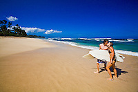 Surfer couple exchanging kisses on the beach on a gorgeous day at Laniakea Beach on the North Shore of Oahu, Hawaii