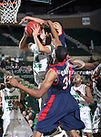 North Texas Mean Green guard Tristan Thompson (14) drives in past South Alabama Jaguars forward Javier Carter (32) during the NCAA  basketball game between the South Alabama Jaguars and the University of North Texas Mean Green at the North Texas Coliseum,the Super Pit, in Denton, Texas. UNT defeated South Alabama 82 to 79...