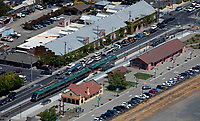 aerial photograph of a Sonoma-Marin Area Rail Transit (SMART) train stopping in Petaluma, Sonoma county, California.  The Petaluma Visitor Center and the Petaluma Art Center are adjacent to the rail line.