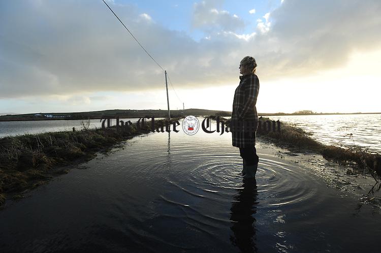 Assumpta Ui Choincheannain, Coiste member of Colaiste Eoghain Ui Chomhraidhe, Carrigaholt, checks on the water levels on the flooded road going to the college. Photograph by John Kelly.