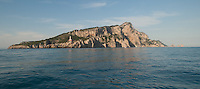 Punta Carena Lighthouse, on the westernmost cape of the rocky Isle of Capri, Italy, guards the entrance to the Gulf of Naples. The famous Faraglion Rocks are seen at the opposite end of the island.