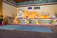 Myanmar, Burma.  Shwedagon Pagoda, Yangon, Rangoon.  Reclining Buddha, Monk in Meditation.