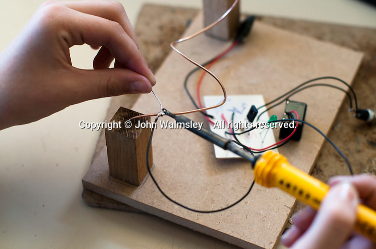 Solering electrical components together to make a buzzbox, Design Technology class, state secondary school.
