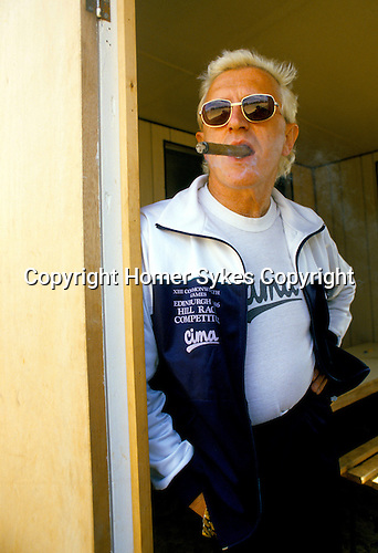 Jimmy Saville, Roundhay, Leeds,UK  Yorkshire 1980s smoking his trademark cigar. Standing at his kitchen door that led onto a small balcony of his apartment that over looked the park.