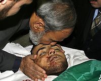 "Gaza.15.01.2008Senior Palestinian leader of the Islamic group Hamas Mahmoud Zahar mourns over the body of his son Hussam, 24, during his funeral in Gaza City, Tuesday, Jan. 15, 2008. Thousands of angry mourners marched through Gaza to bury the son of Gaza's most senior Hamas leader, alongside 16 other Palestinians, mostly militants, in an Israeli incursion into the strip on Tuesday. Hussam Zahar, 24, was the second son of Hamas hard-liner Mahmoud Zahar, to be killed by Israel. Zahar is Hamas' most senior member in the Gaza Strip, where the militant group rules. ""photo by Fady Adwan"