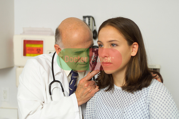 older male doctor examining ear of adolescent girl with otoscope