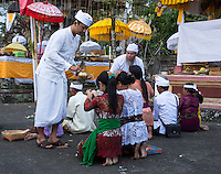 Bali, Indonesia.  Hindu Priest Blessing Worshipers with Holy Water.  Pura Dalem Temple.  Dlod Blungbang Village.