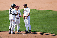 Grant Gordon (35) of the Missouri State Bears talks with Catcher Luke Voit (30) and Head Coach Keith Guttin (2) during a game against the Wichita State Shockers on April 9, 2011 at Hammons Field in Springfield, Missouri.  Photo By David Welker/Four Seam Images