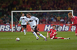 Germany's Lukas Podolski leaves Aaron Ramsey on the floor during the FIFA 2010 World Cup Qualifier match between Wales and Germany at the Millennium Stadium in Cardiff..