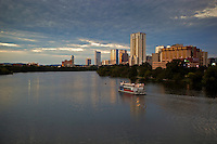 A cruise ship steams along Lady Bird Lake in downtown Austin, Texas.