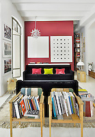 A contemporary living room with barrel ceiling. The room is white with vibrant accent colours. A black sofa provides a strong colour contrast against a coral pink wall. Two simple wooden armchairs become a novel place to display books.
