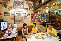 """Thailand. Bangkok. The family Saengurai sits at the table in her rented house. The family is afraid of losing their home because of a development master plan of the Bangkok Metropolitan Administration (BMA). The family of chinese origin has been living in Tha Tian in a shophouse for generations. Food on table and television.  A picture of King Bhumibol is taped on the wall. Bhumibol Adulyadej (born 5 December 1927), is the current King and Head of the State of Thailand. Publicly acclaimed """"the Great"""" he is also known as Rama IX. Having reigned since 9 June 1946, he is the world's longest-serving current head of state and the longest-serving monarch in Thai history. Tha Tian is a community located in the downtown area and in the center of the urban historic district, called Koh Rattanakosin. 02.04.09 © 2009 Didier Ruef"""