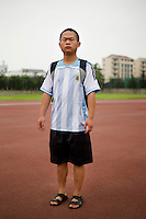 """Bill Chenxiaohu, a student, age 23, poses for a portrait in Nanjing. Response to 'What does China mean to you?': '""""Central"""" means """"moderate."""" China is a country that upholds the Buddhist Doctrine of the Mean. """"Mean"""" is just normal.'  Response to 'What is China's role in the future?': 'This nation will rise up.'"""