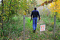 00105-049.11 Bowhunting: Archer walks trail toward archery practice range during early fall.  Danger sign.  Warning.
