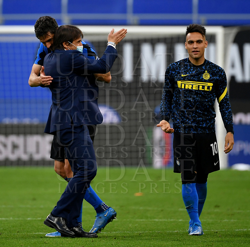 Inter Milan's coach Antonio Conte wears a protective mask as he congratulates with his players Roberto Gagliardini, left, and Lautaro Martinez, at the end of the Italian Serie A football match between Inter Milan and Sampdoria at Milan's Giuseppe Meazza stadium, May 8, 2021. Inter won his 19th Scudetto.<br /> UPDATE IMAGES PRESS/Isabella Bonotto