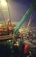 "Crewmen onboard the fishing vessel ""Kiska Sea"" look for their crab pot buoys in the arctic ice pack of the Bering Sea during the opilio crab season in January and February of 1995.  The Bering Sea is known for having the worst storms in the world.  Nights are long and cold in the arctic in the winter.  Crab fishing in the Bering Sea is considered to be one of the most dangerous jobs in the world.  This fishery is managed by the Alaska Department of Fish and Game and is a sustainable fishery.  The Discovery Channel produced a TV series called ""The Deadliest Catch"" which popularized this fishery. Today this fishery, largely based out of Dutch Harbor, AK has been consolidated resulting in a lot less boats fishing."