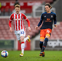 20th February 2021; Bet365 Stadium, Stoke, Staffordshire, England; English Football League Championship Football, Stoke City versus Luton Town; Glen Rea of Luton Town passes the ball in front of Sam Clucas of Stoke City