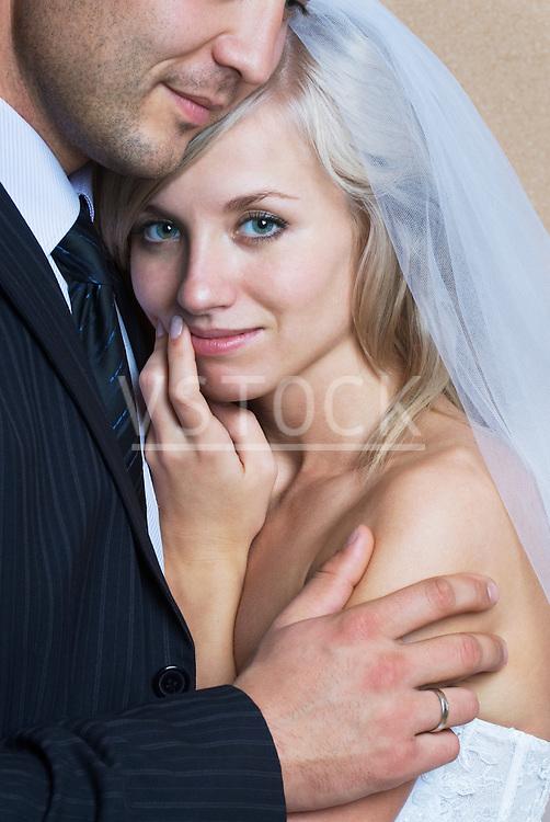 Bride and groom embracing, portrait
