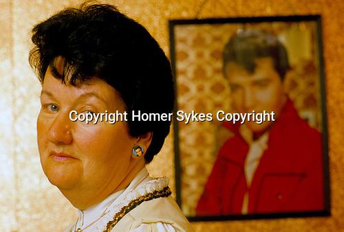 'ELVIS FANS', VALERIE CONSTABLE WEARING ELVIS PRESLEY EARRINGS IN HER SOUTH LONDON FLAT