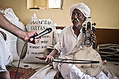 Ashutosh Sharma of Amarrass records pulls the microphone closer to 75-year-old Manganiyar artist, Saqar Khan while he sings and plays his Kamancha (music instrument) inside his house in Hamira village of Jaiselmer district in Rajasthan, India. Photo: Sanjit Das/Panos