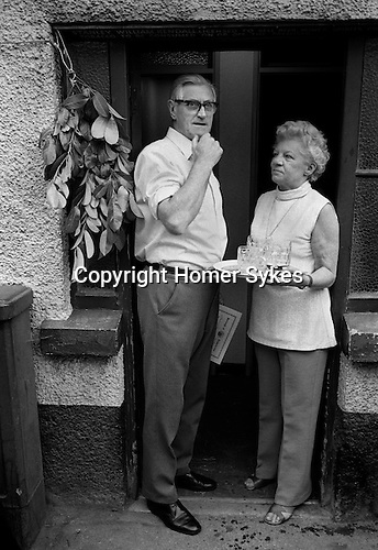 Ashburton Court Leet. Devon 1975<br /> Publican Stanley Kendall and his wife, with empty beer glasses.  A sprig of greenery is hung form the door of the pub, to indicate that the ale has been tasted and considered fit for consumption.<br /> <br /> A Court Leet was a manorial court that dealt with petty offences in the community and enforced regulations regarding the quality of staples, such as bread and ale. Over the years with the reorganisations of local government, their powers have been diminished. They are now purely ceremonial.  Ashburton Court Leet preserves some of the past. A meeting is held each November on the fourth Tuesday in St Lawrence's Chapel attended by the freeholders of the town.  They elect a Portreeve the equivalent of a mayor along with officers whose job is to taste the ale, weigh the bread. Pig drivers, scavengers and surveyors of the markets and watercourses are also elected.<br /> <br /> During the annual fair they visit all the pubs, and hotels of the town in turn and give a certificate and a sprig of evergreen to each landlord who ale is up to standard, to display above the door. Loaves of bread are also weighed and tasted. Originally quality control measures such as these were made to ensure that customers got a fair deal and were not be given short measure.