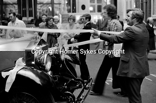 Caxton Hall Westminster London. Tying a white ribbon, a good luck ritual around the hired Rolls Royce car. 1970s 1972 London .