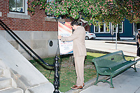 A worker adjusts a sign that blew over in the wind before Texas senator and Republican presidential candidate Ted Cruz speaks at a town hall put on by the Concerned Veterans for American at Milford Town Hall in Milford, New Hampshire.