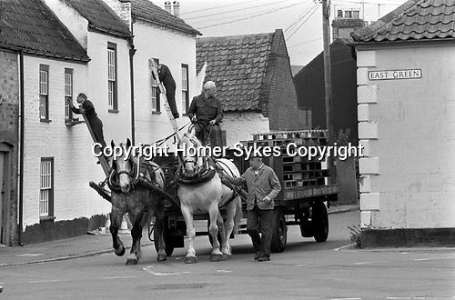 Dray horses 1980s Southwold Suffolk East Angelia. Men finished delivering crates barrels of beer, lorry with just wooden pallets. 1985 Men painting the building behind. UK