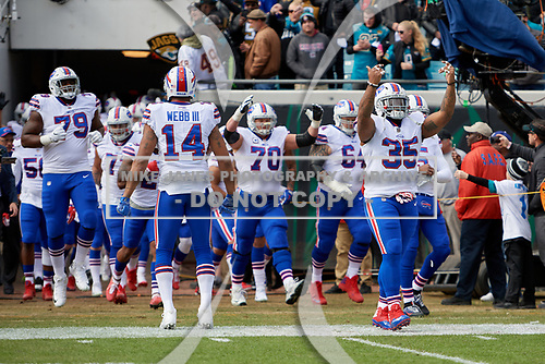 Buffalo Bills, lead by Joe Webb (14) and Mike Tolbert (35), take the field during introductions before an NFL Wild-Card football game against the Jacksonville Jaguars, Sunday, January 7, 2018, in Jacksonville, Fla.  (Mike Janes Photography)
