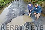Concerned residents John Reidy and Pat O'Hara examine the deep pot hole in Glandahalin in Ballyheigue on Monday.